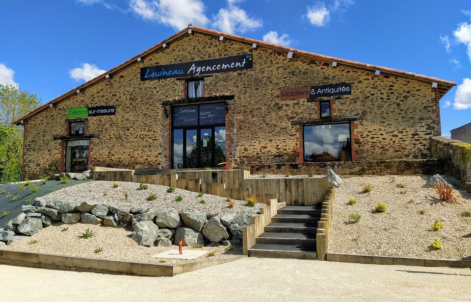 Façade du magasin Louineau Agencement aux Essarts en Bocage en Vendée : Vente d'antiquités et magasin de meubles.